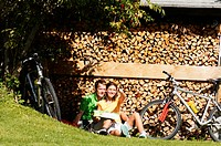 Couple sitting on stack of firewood, man pointing