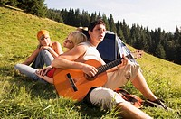 Young people in meadow, man playing guitar, tilt view