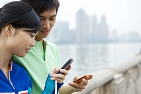 Young couple, each looking at cell phone, cityscape in background