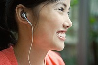 Young woman wearing earphones, smiling, close-up, profile