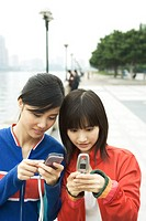 Two young women using cell phones