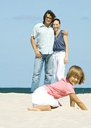 Girl digging in sand while parents stand in background