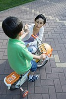 Boy on bike with training wheels and mother