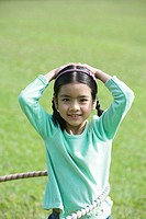 Girl playing with plastic hoop, smiling at camera