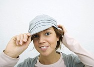 Young woman adjusting cap, portrait