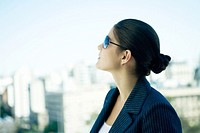 Woman wearing sunglasses, looking up, skyline in background, profile