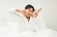 woman in white pajamas waking up in her bed in the morning