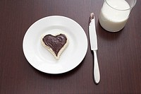 still life of sandwich with spread cut out in shape of heart on plate and glass of milk