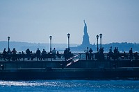 USA, New York, people walking by water, statue of libery, outdoors