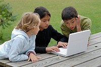 Children 6-13 using laptop in garden