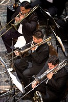 Male trombone players performing in orchestra, elevated view