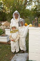 Beekeeper and sons 7-12 standing amongst hives, portrait