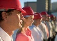 Group of business people wearing hard hats, side view