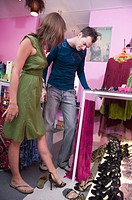 Young couple in shoe shop, woman trying on shoes