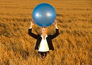 Businesswoman carrying fitness ball on head in oats field, eyes closed