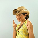 Woman in cowboy hat with fingers held as guns, portrait
