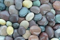 Wet shiny granite pebbles on beach, full frame