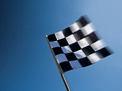 Checkered flag waving against clear sky, close-up,