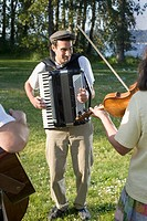 Young man playing accordian in park
