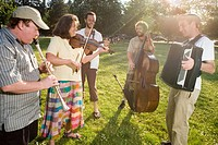 Musicians playing music in park, smiling