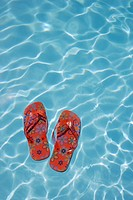 Flip-flops floating in swimming pool