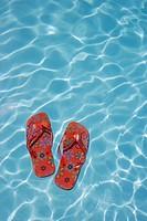 Flip-flops floating in swimming pool