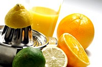 Close-up of juicer with citrus fruits and a glass of juice