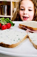 Close-up of a girl looking at a slice of bread and fruit with her mouth open