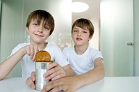 Portrait of two boys opening a can of food