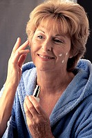 Close-up of a mature woman applying cream on her face