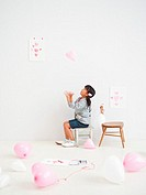 Girl playing heart-shaped balloons
