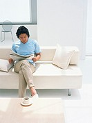 Man reading newspaper on sofa
