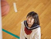 Smiing teenagegirl playing basketball
