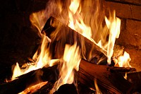 fire in stone or brick fireplace, glimpse of glowing coals, yellow-white flames