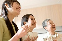 Three generation family having meal, smiling and looking up, side view, low angle view