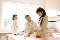 Three generation family in kitchen, smiling, front view, side view