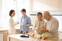 Two couples in kitchen, senior woman lecturing senior man, front view, side view