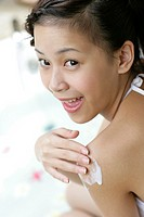 View of a young woman applying a cream on body