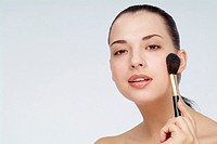 Close-up of a young woman holding makeup brush
