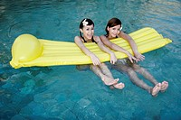 Two teenage girls with float in swimming pool (thumbnail)