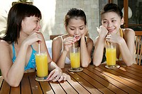 Three teenage girls with juice glasses, holding straws