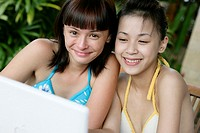 Portrait of two teenage girls wearing bikinis