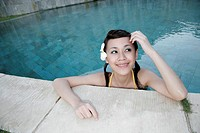 Portrait of a teenage girl leaning by a swimming pool