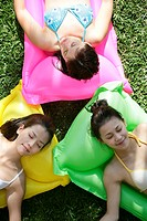 View of three teenage girls lying on floats