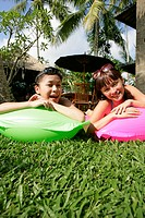Portrait of two teenage girls lying on floats