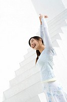 A woman smiling and stretching arms at the stairs, side view, low angle view