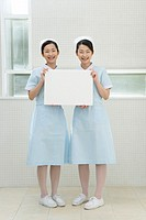 Portrait of two nurses, twin sisters, holding a blank board, front view