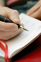 Close-up of a person's hand writing in a diary
