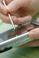 Close-up of a person's hand operating a mobile phone