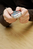 Close-up of a man's hand operating a remote control